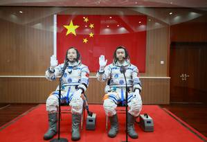 Os astronautas Jing Haipeng e Chen Dong acenam em frente à bandeira chinesa antes da partida da nave Shenzhou-11 Foto: CHINA STRINGER NETWORK / REUTERS