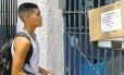 Aluno lê aviso sobre aula suspensa na Faetec de Marechal Hermes