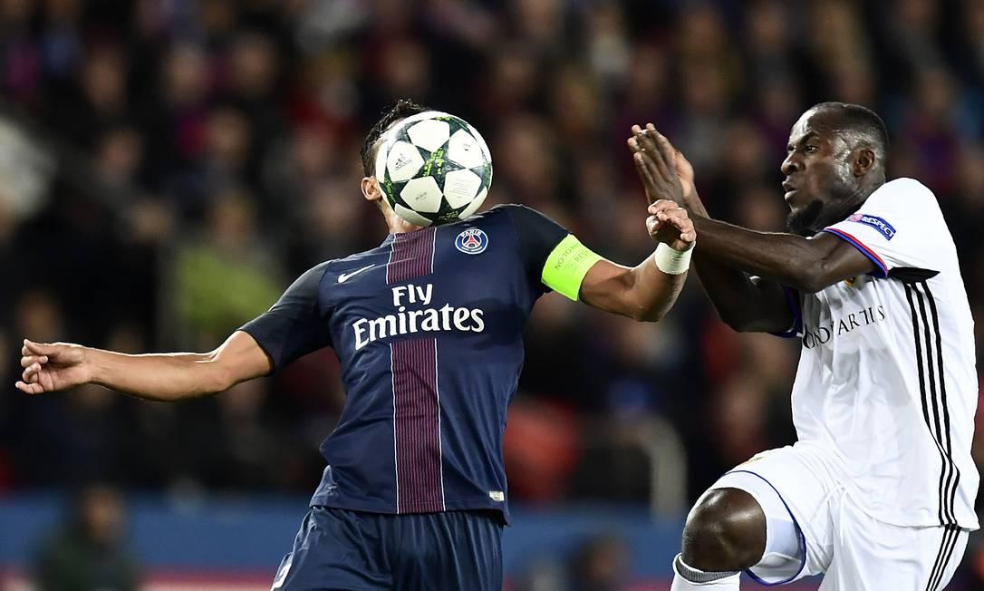 O brasileiro Thiago Silva, do Paris Saint-Germain, domina a bola, marcado pelo atacante Seydou Doumbia, do Basel, no Parque dos Príncipes MIGUEL MEDINA / AFP