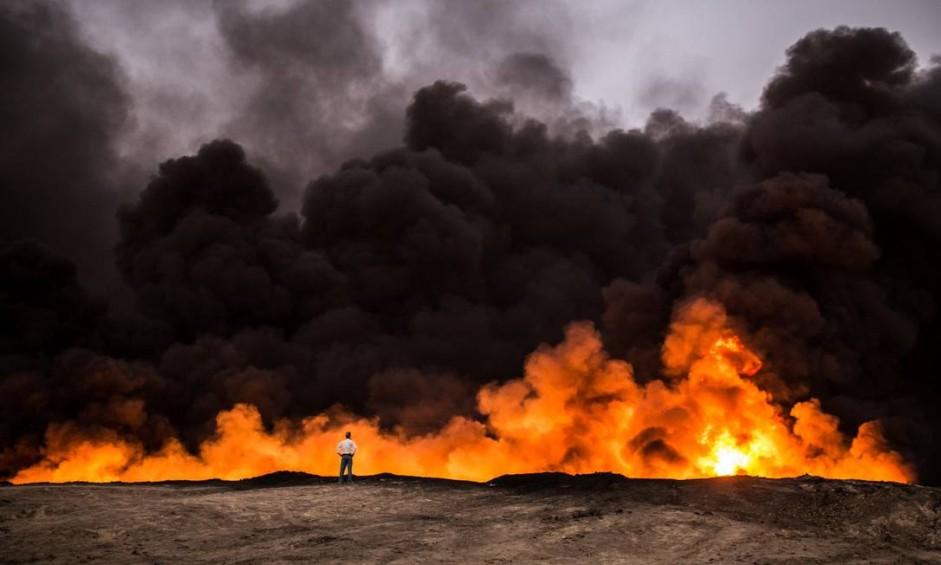 Homem obeserva um oleoduto incendiado na área de Qayyarah, cerca de 60 quilômetros ao sul de Mosul, durante uma operação das forças iraquianas contra Estado Islâmico Foto: YASIN AKGUL / AFP
