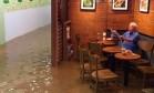 Idoso ignora enchente e continua tomando café e lendo jornal em lanchonete Foto: Reprodução/Facebook