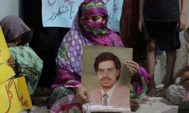 Mulher de Ali segura retrato do marido Foto: AP
