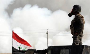 Soldado iraquiano usa máscara contra gases para se proteger da fumaça tóxica de fábrica incendiada pelo EI perto da base de Qayyarah Foto: AHMAD AL-RUBAYE / AFP/AHMAD AL-RUBAYE