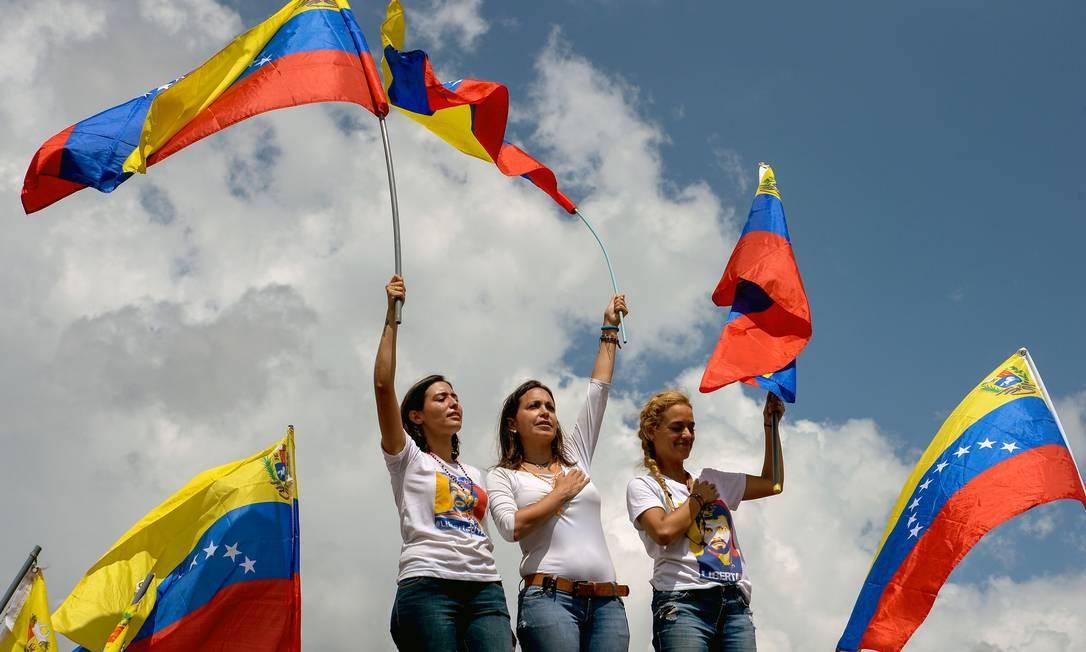Patricia Gutiérrez, mulher do ex-prefeito Daniel Ceballos (esquerda), a ex-deputada Maria Corina Machado (centro) e Lilian Tintori, casada com Leopoldo López, levam bandeiras da Venezuela em protesto Foto: FEDERICO PARRA / AFP