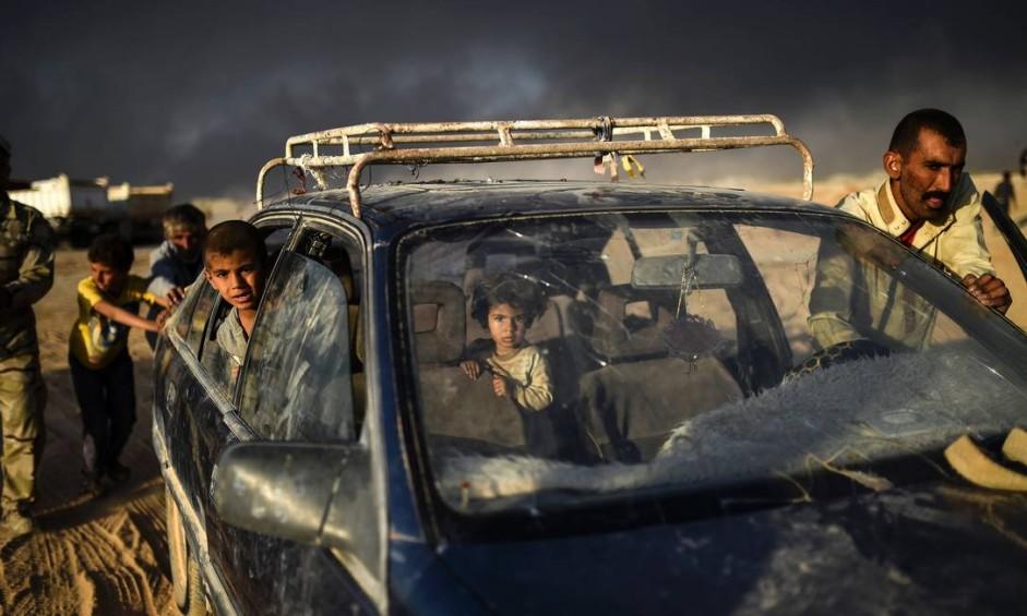 Iraquianos deslocados por causa da guerra contra o Estado Islâmico, chegam ao campo de refugiados na cidade de Qayyarah, ao sul de Mossul Foto: BULENT KILIC / AFP