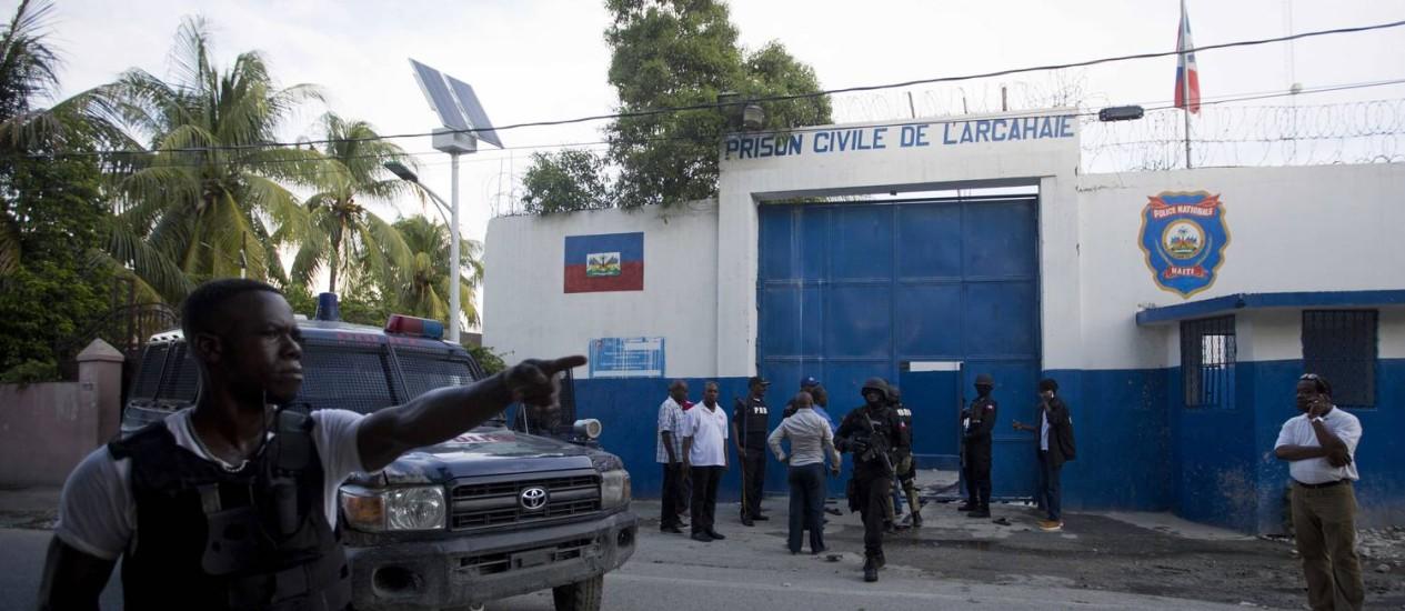 Policiais haitianos se reúnem no portão da prisão da cidade litorânea de Arcahaiea, de onde mais de 170 detentos fugiram durante rebelião Foto: Dieu Nalio Chery / AP/Dieu Nalio Chery