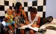 Mônica ajuda o filho Luiz Carlos nos estudos: ela reivindica atividades extras no período escolar Foto: Domingos Peixoto / Agência O Globo