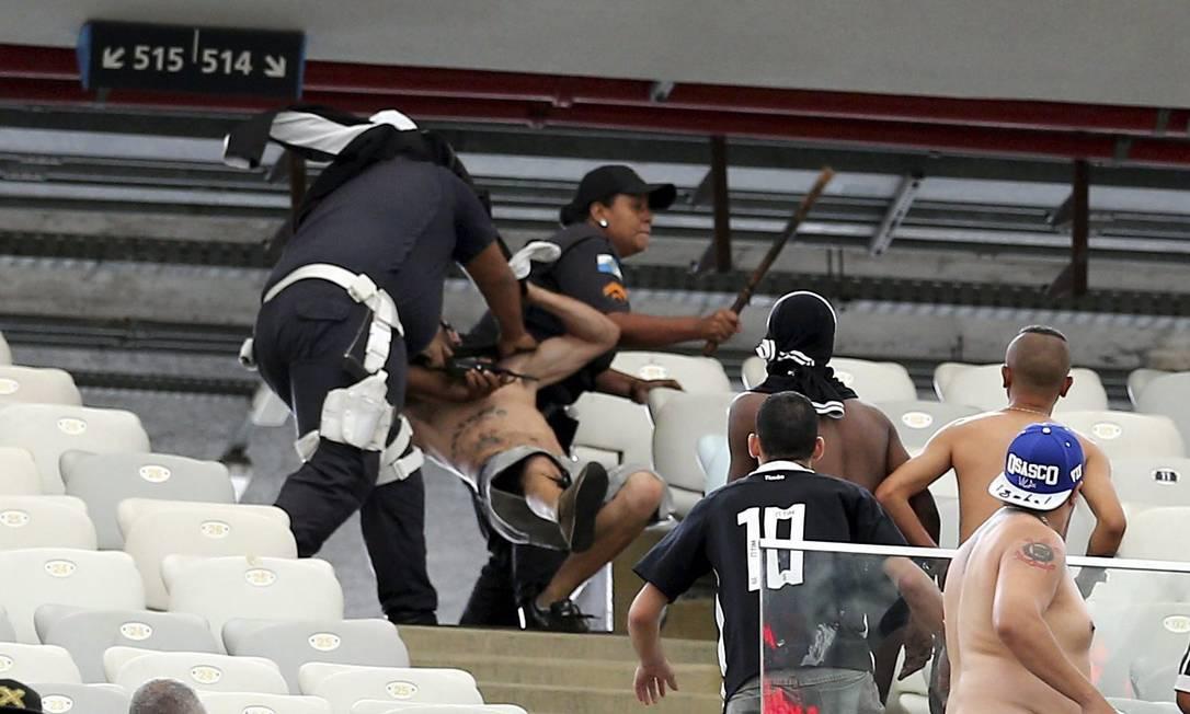 Policial tenta imobilizar um torcedor corintiano Marcelo Carnaval / Agência O Globo