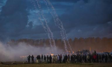 Clima tenso. Bombas de gás lacrimogêneo são atiradas pela polícia francesa durante confronto com migrantes no acampamento improvisado de Calais: esvaziamento começa hoje Foto: Emilio Morenatti / Emilio Morenatti/AP