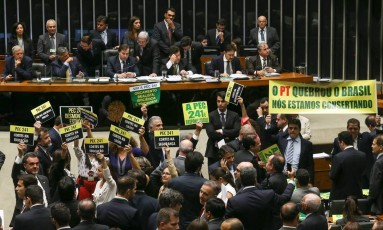 Aprovado. Deputados da base governista e da oposição erguem faixas e cartazes durante a 1ª sessão de votação da PEC 241 na Câmara, no início de outubro Foto: André Coelho / André Coelho/10-10-2016