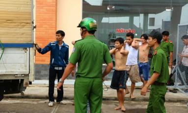 Policiais escoltam dependentes químicos que fugiram de centro de reabilitação e foram recapturados Foto: VIETNAM NEWS AGENCY / AFP