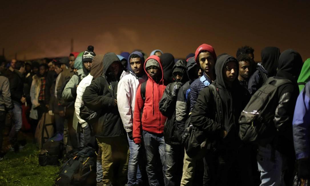 Migrantes aguardam em fila para se registrarem Foto: Emilio Morenatti / AP