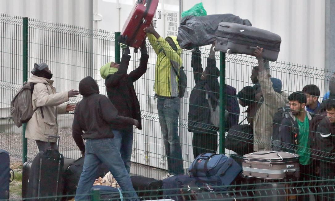 Migrantes passam bagagem para amigos por cima de uma cerca durante processo de registro Foto: Thibault Camus / AP