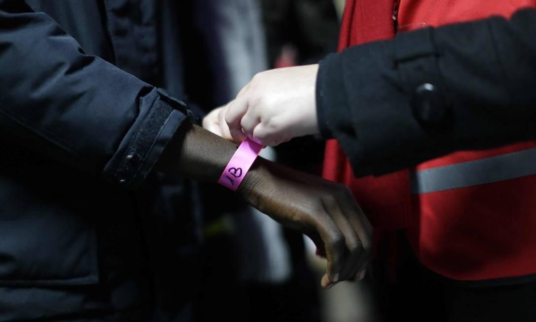 Imigrante recebe pulseira para ser retirado de Calais. Autoridades estimam que até oito mil pessoas estão no campo Foto: Emilio Morenatti / AP