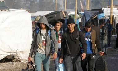 Migrantes carregam seus pertences durante operação de desmantelamento do campo de Calais Foto: PASCAL ROSSIGNOL / REUTERS