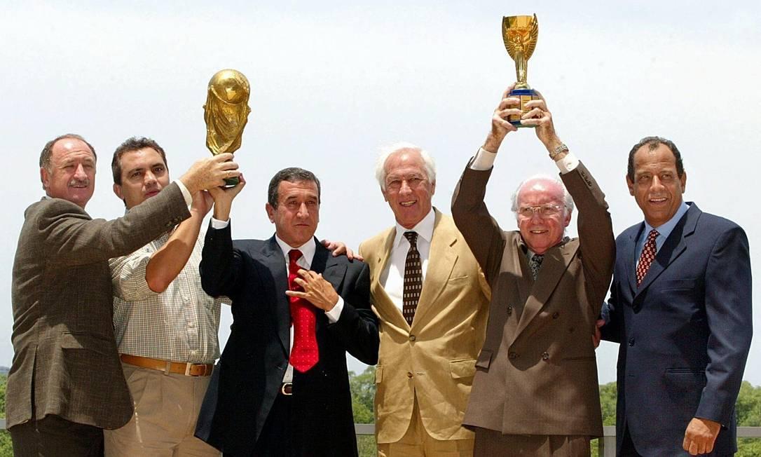 Em 2002, Carlos Alberto Torres (último à direita) posa com Bellini e Branco, capitães que também levantaram Copas do Mundo, e com os então treinadores Felipão, Parreira e Zagallo: comemoração pelo penta Antonio Scorza / AFP