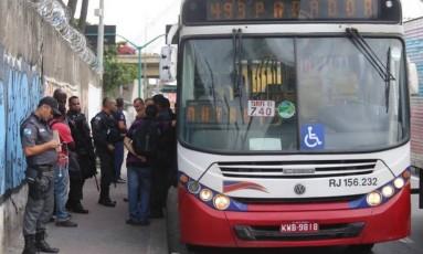 Policiais com o ônibus na Avenida Brasil Foto: Fabiano Rocha / Extra