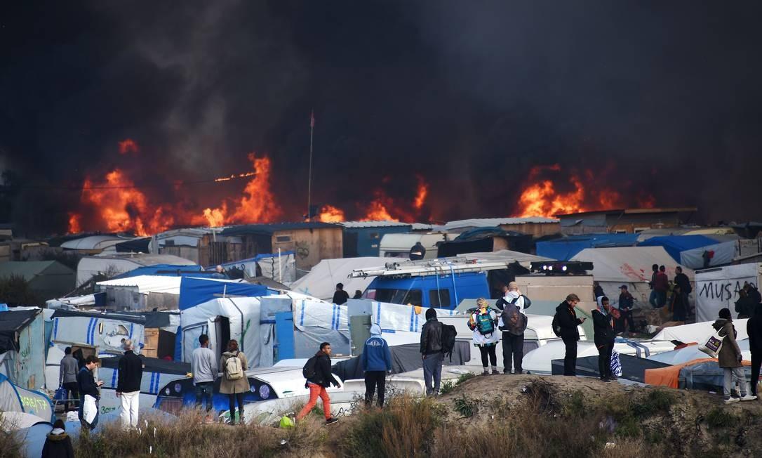 Fumaça preta encobre abrigos improvisados no terceiro dia de desmantelamento da 'Selva'; cerca de 4 mil pessoas já deixaram campo de refugiados Foto: DENIS CHARLET / AFP