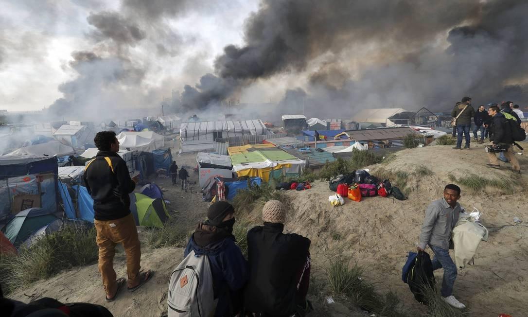 Jornalistas e imigrantes observam a polêmica destruição do campo de Calais; refugiados são transferidos a outros centros de acolhimento pela França Foto: PHILIPPE WOJAZER / REUTERS
