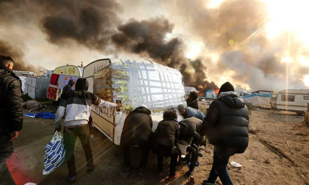 Pessoas tentam mover caravana na 'Selva'; autoridades francesas pretendem finalizar ainda nesta quarta-feira as operações de esvaziamento Foto: FRANCOIS NASCIMBENI / AFP