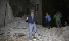 Moradores passam por escombros em Visso Foto: Matteo Crocchioni / AP
