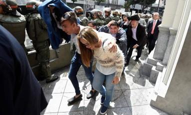 Legisladores da oposição se protegem enquanto tentam chegar à Assembleia Nacional em Caracas Foto: JUAN BARRETO / AFP