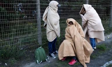 Migrants se protegem do frio durante o desmantelamento da 'Selva' em Calais Foto: PHILIPPE WOJAZER / REUTERS