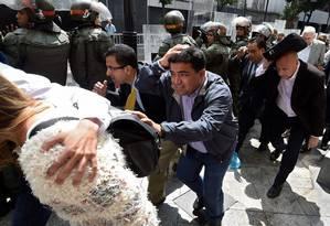 Sob ameaça. Legisladores da oposição se protegem, atrás de uma barreira policial, da hostilidade de manifestantes chavistas, ao entrarem na Assembleia Nacional em Caracas Foto: JUAN BARRETO / JUAN BARRETO/AFP