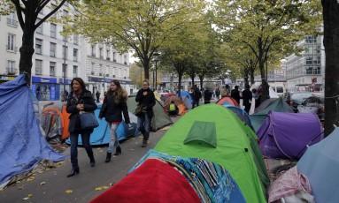 Pessoas caminham entre tendas improvisadas por refugiados em ruas de Paris Foto: Christophe Ena / AP