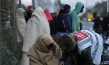 Um trabalhador humanitário ajuda um migrante que passou a noite na rua após o desmantelamento do campo de Calais, no Norte da França Foto: PHILIPPE WOJAZER / REUTERS