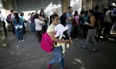 Mulher carregando seu bebê passa por uma fila de pessoas em frente a uma farmácia em Caracas Foto: Ariana Cubillos / AP