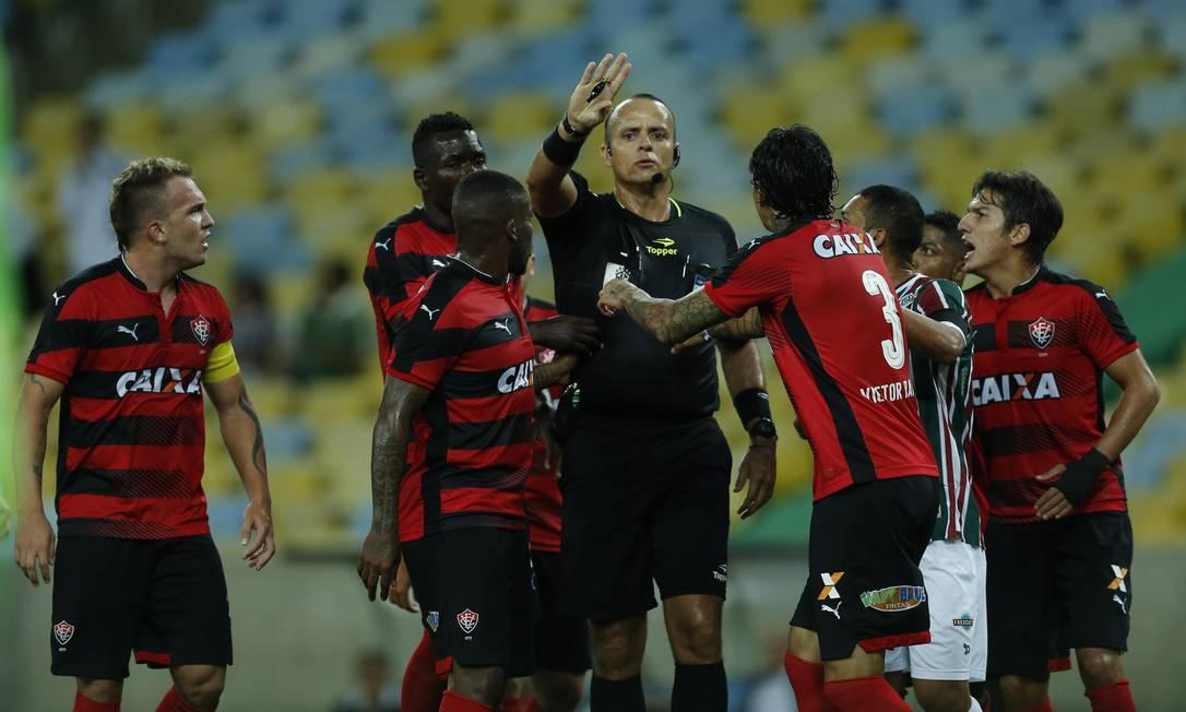 Árbitro Nielsen Nogueira é cercado por jogadores do Vitória ao marcar pênalti fora da área para o Fluminense Alexandre Cassiano / Agência O Globo