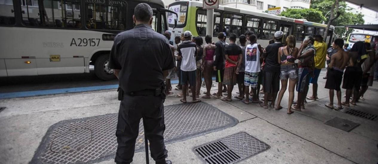 Tensão. PM vigia ponto do ônibus 474 em Copacabana: cenas de violência fazem parte da rotina de quem usa a linha Foto: Alexandre Cassiano