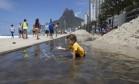 Crianças aproveitam as montanhas de areia e as piscinas formadas na pista Foto: Márcia Foletto / Agência O Globo