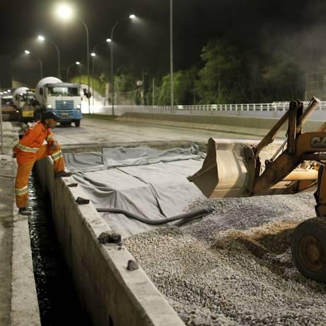 Obstáculo na via. Homens trabalham para tapar o buraco no Novo Joá Foto: Gabriel de Paiva