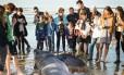 Curiosos observam o corpo do tubarão frade com três metros de comprimento