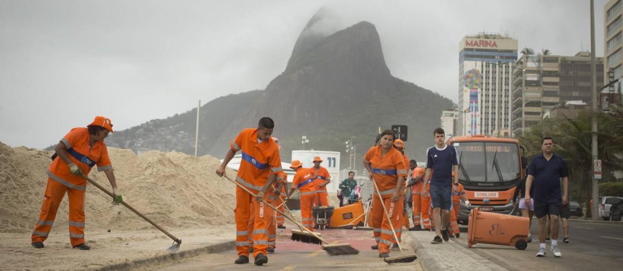 Garis da Conlurb continuam o trabalho de llimpeza da areia que invadiu a ciclovia e o calçadão do Leblon Foto: Márcia Foletto / Agência O Globo
