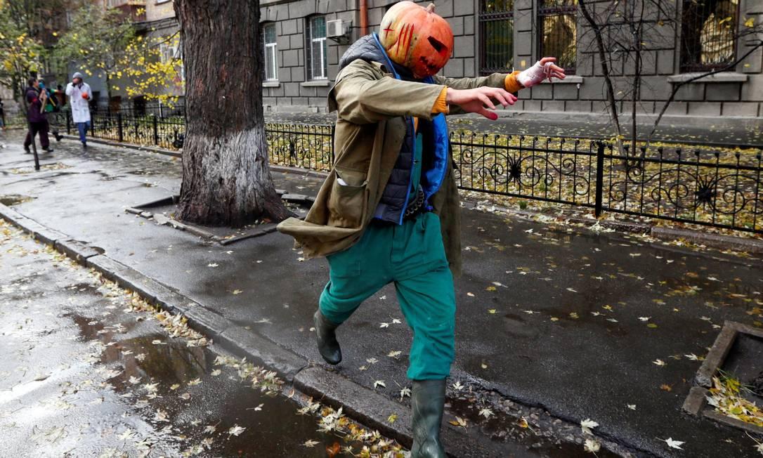 Homem, com uma abóbora na cabeça, corre pela rua durante as celebrações do Dia das Bruxas em Kiev, Ucrânia 30 de outubro de 2016 VALENTYN OGIRENKO / REUTERS