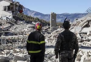 Terra arrasada. Bombeiro e soldado observam destruição em Amatrice, com a Torre do Sino parcialmente afetada: vila já tinha perdido mais de 200 pessoas Foto: Massimo Percossi / Massimo Percossi//AP