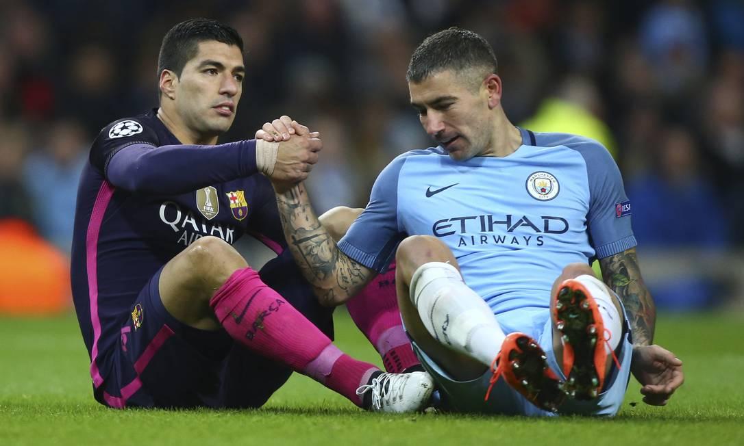 O uruguaio Suárez dá a mão a Aleksandar Kolarov, do Manchester City Dave Thompson / AP