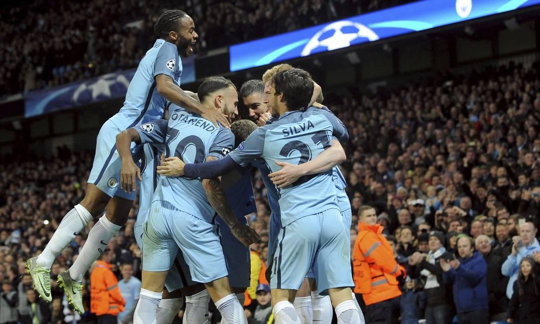 Sterling pula sobre os companheiros na comemoração do segundo gol do Manchester City sobre o Barcelona, marcado por De Bruyne Rui Vieira / AP