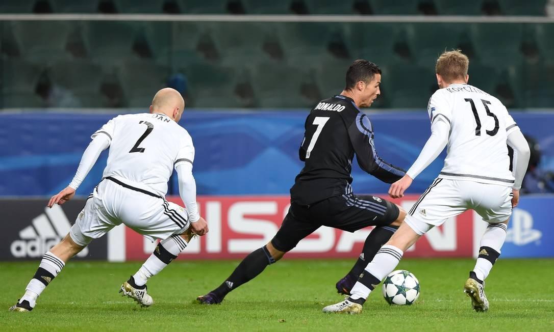 Cristiano Ronaldo avança com a bola, cercado por Pazdan (2) e Kopczynski (15) , do Legia Varsóvia JANEK SKARZYNSKI / AFP