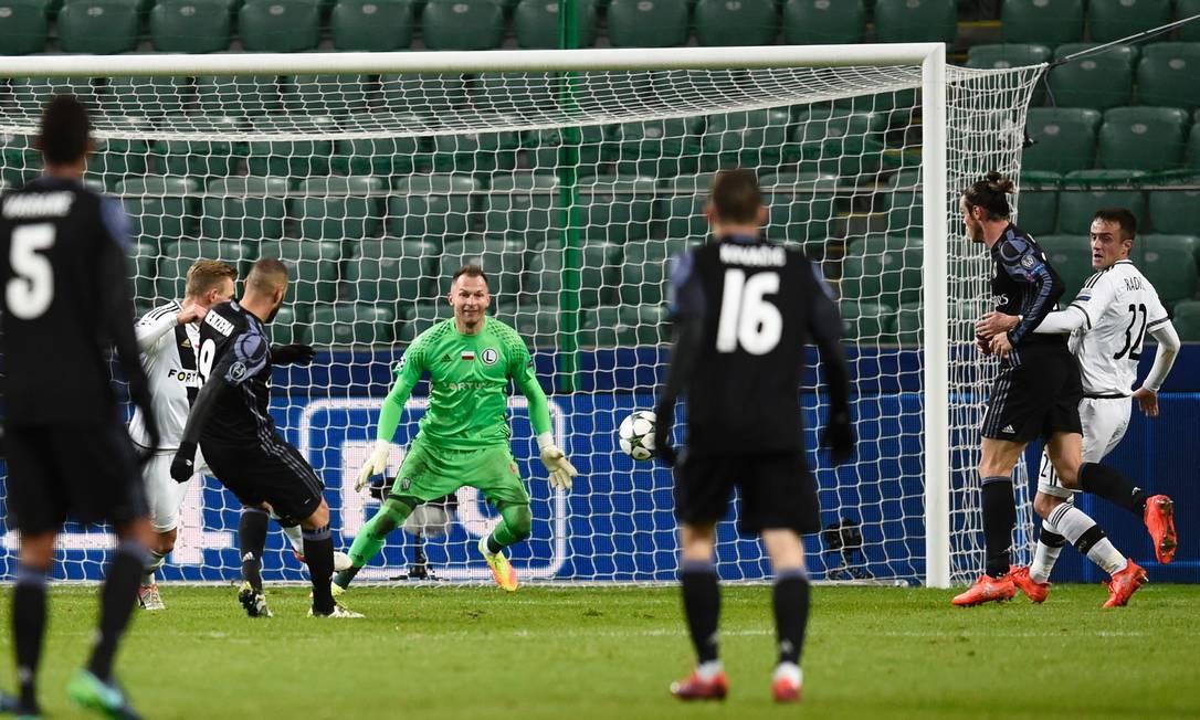 Benzema (9) bate de primeira para marcar o segundo gol do Real Madrid sobre o Legia, em Varsóvia ODD ANDERSEN / AFP