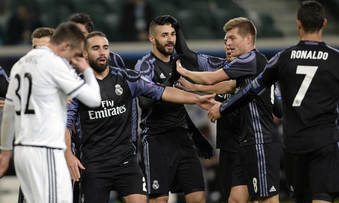 Karim Benzema, no centro da foto, recebe os cumprimentos dos companheiros de Real Madrid após seu gol sobre o Legia Alik Keplicz / AP
