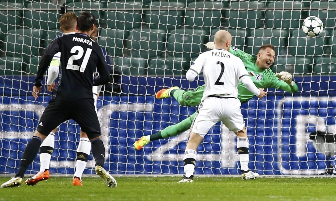 O goleiro do Legia, Malarz, voa para tentar defender chute de Benzema (fora da foto), em ataque do Real Madrid KACPER PEMPEL / REUTERS