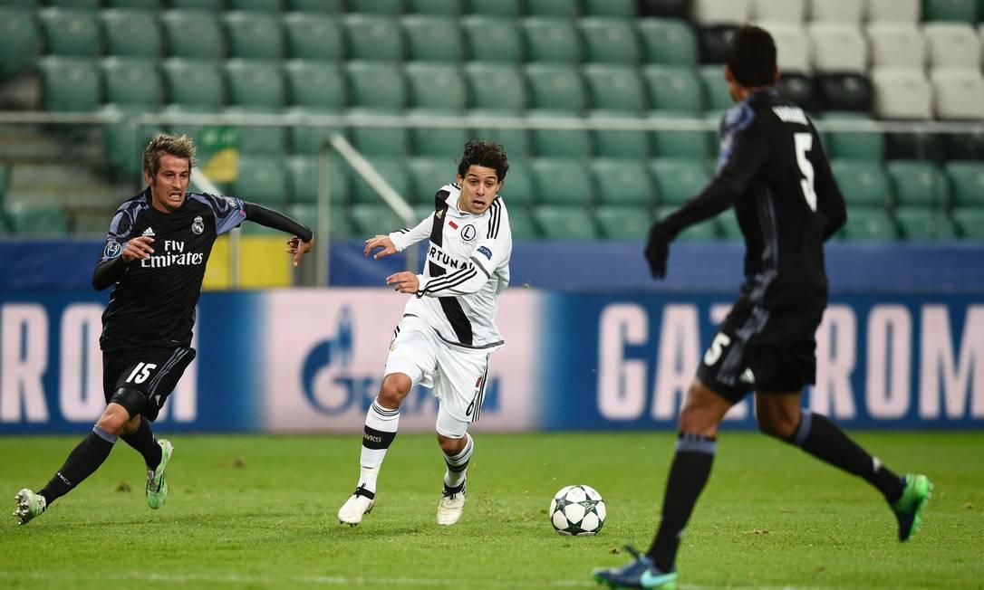 O brasileiro Guilherme, do Legia, é perseguido por Coentrão (15), numa investida contra a defesa do Real Madrid ODD ANDERSEN / AFP