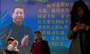Pedestres passam por um cartaz com a foto do presidente Xi Jinping, com texto sobre o Exército de Liberação Popular Foto: THOMAS PETER / REUTERS