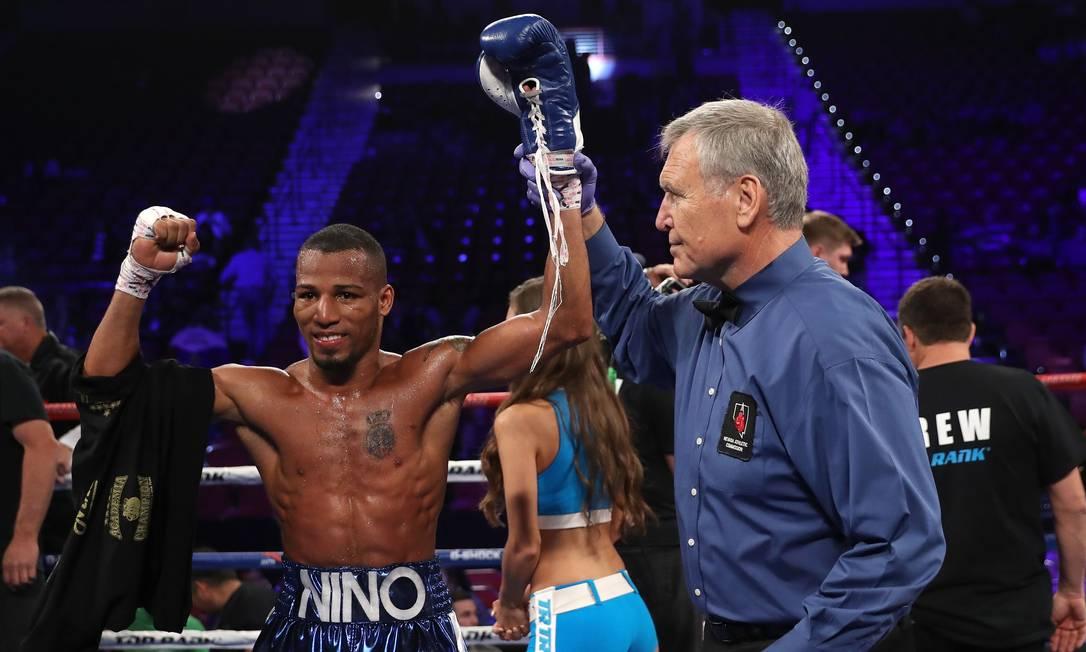 O árbitro ergue o braço esquerdo do brasileiro Robson Conceição em Las Vegas, ao final de sua primeira luta como profissional no boxe, contra Clay Burns Christian Petersen / AFP