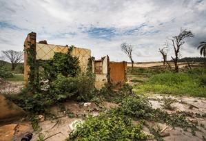 Bento Rodrigues. A lama ainda domina a paisagem, composta de umas poucas árvores, escombros do que restou das casas e, ao fundo, o dique ainda em construção Foto: Ana Branco