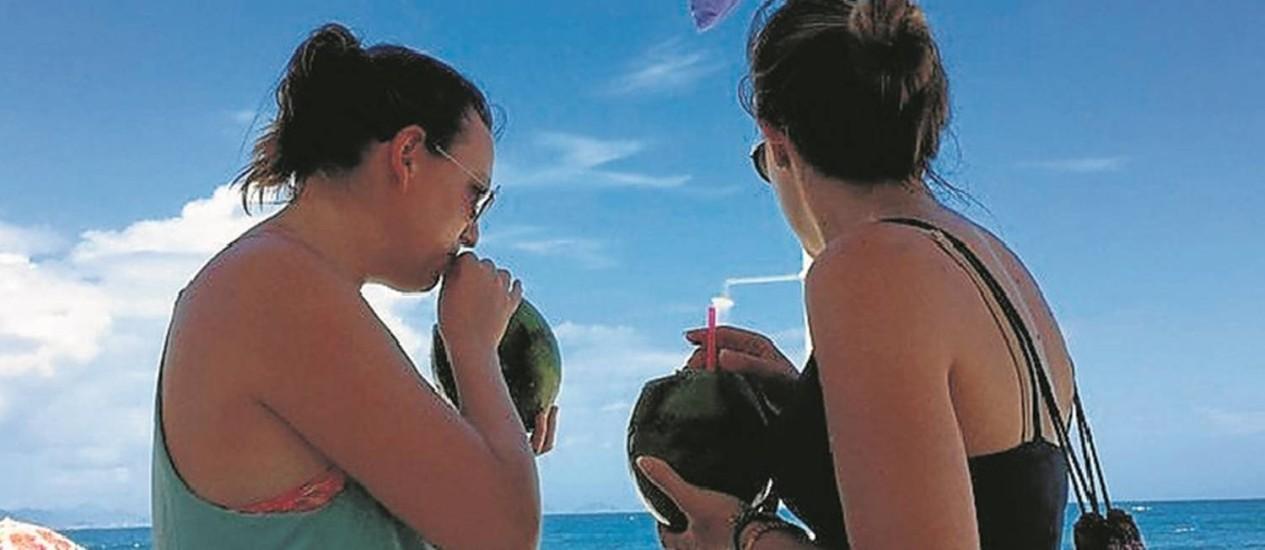 Refresco caro. Turistas bebem água de coco na Praia de Copacabana Foto: Guilherme Ramalho